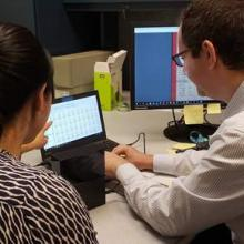 An image of ARMS Staff assisting a Researcher find records from the online archival collections