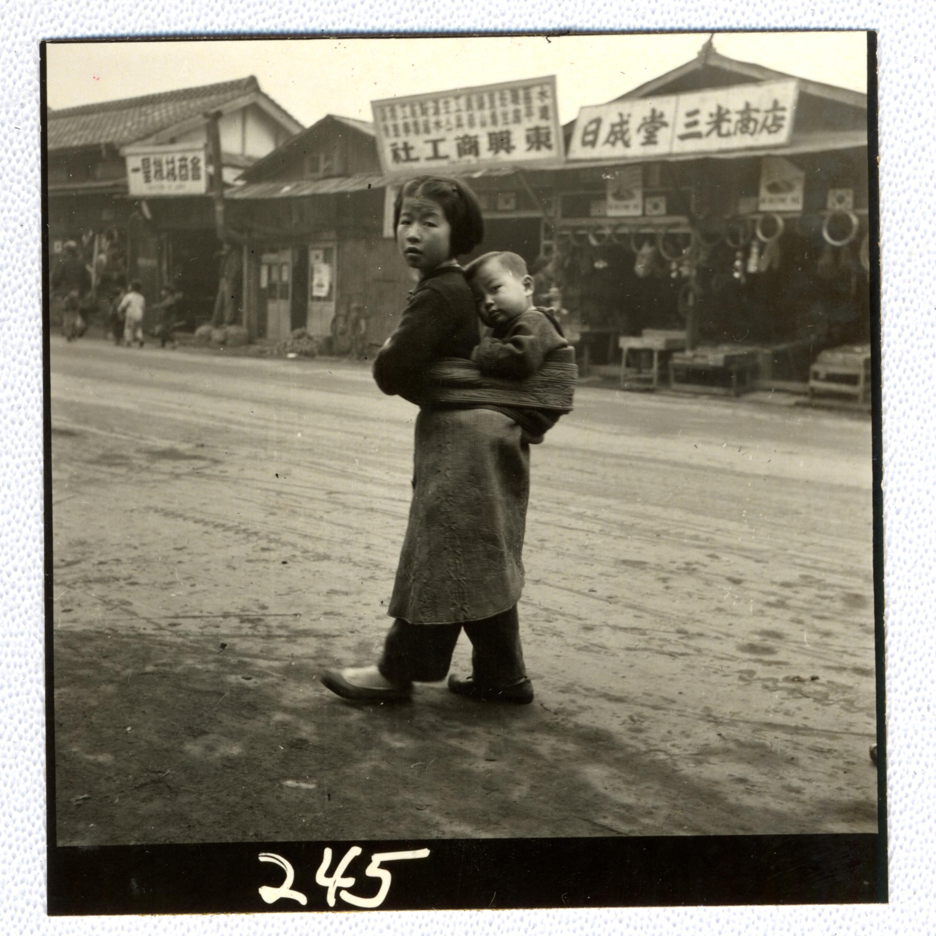 In this photo, a scene typical of any place in Korea--a young girl carrying her smaller brother in a sling tied around her waist.